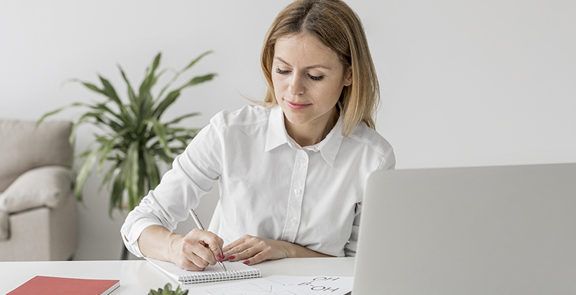Image: Woman Writing Notes on Laptop